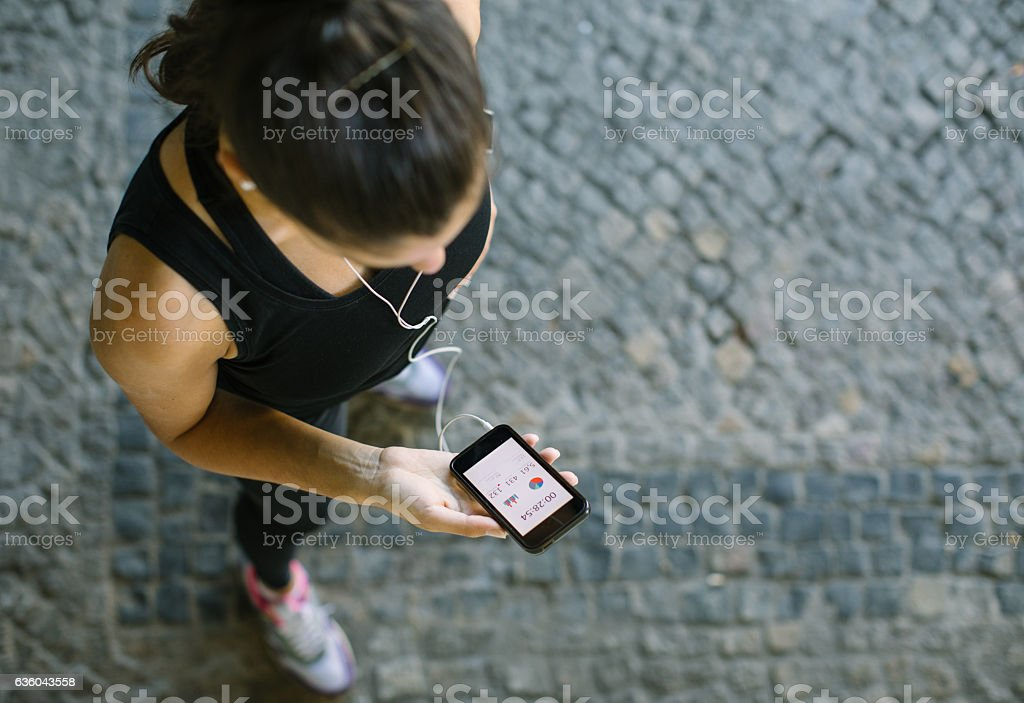 Woman monitoring her workout progress on fitness app - Photo