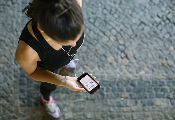 woman monitoring her workout progress on fitness app - application mobile photos et images de collection