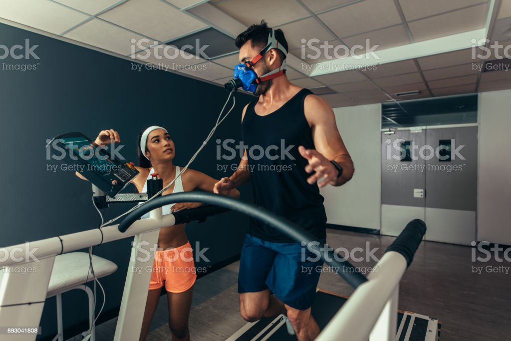 Woman monitoring runner with mask on treadmill stock photo