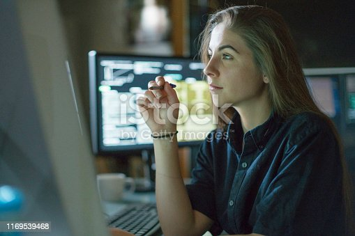 A young woman is seated at a desk surrounded by monitors displaying data, she is contemplating in this dark, moody office.