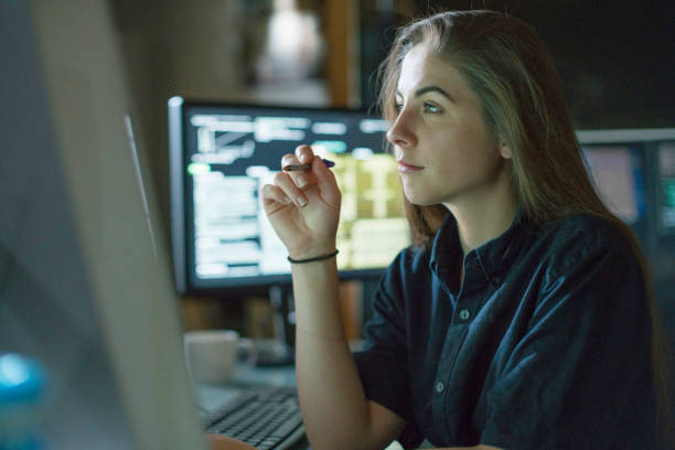 Woman monitors dark office A young woman is seated at a desk surrounded by monitors displaying data, she is contemplating in this dark, moody office. data stock pictures, royalty-free photos & images