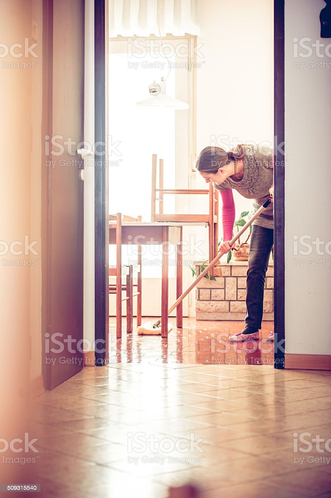 Woman Mopping Under Dining Table stock photo
