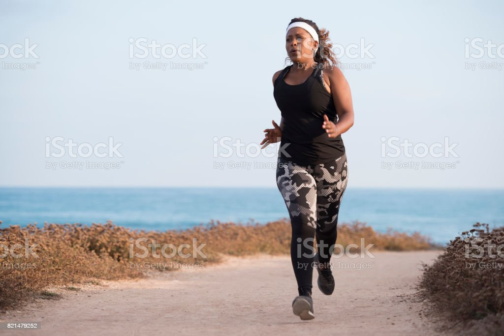 A young plump black woman running along the sea coastline.
