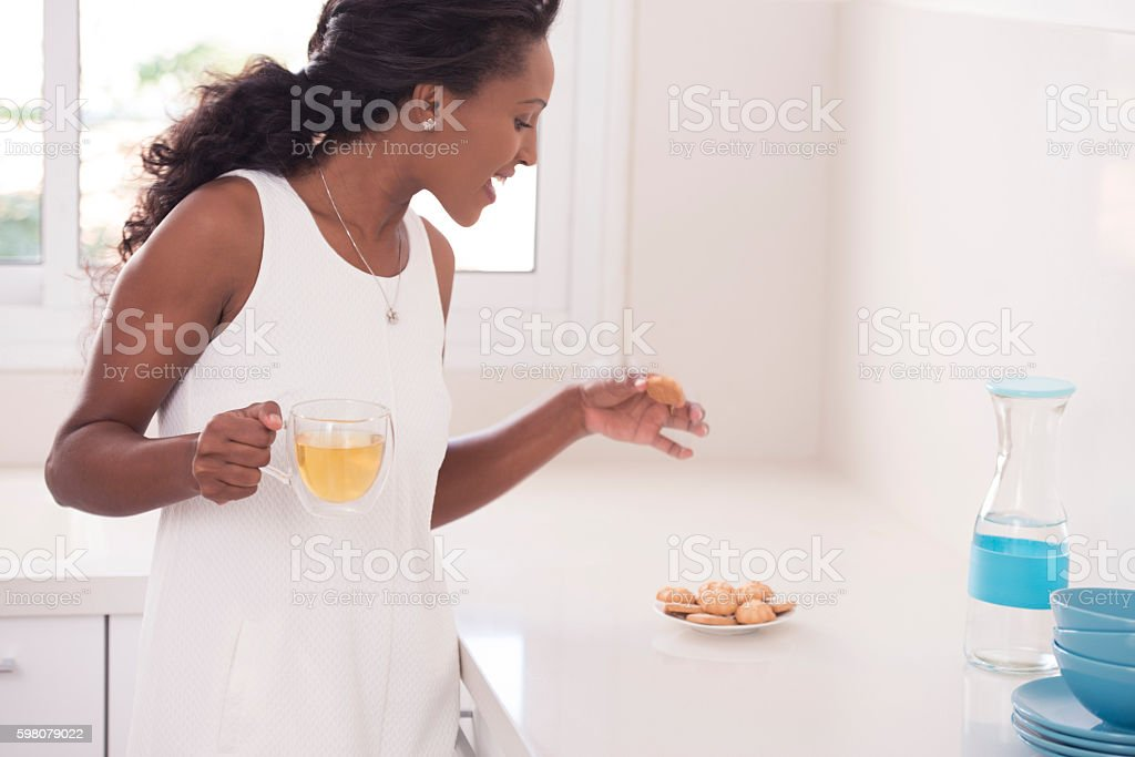 An attractive woman holding cup of green tea and eating shortbread.