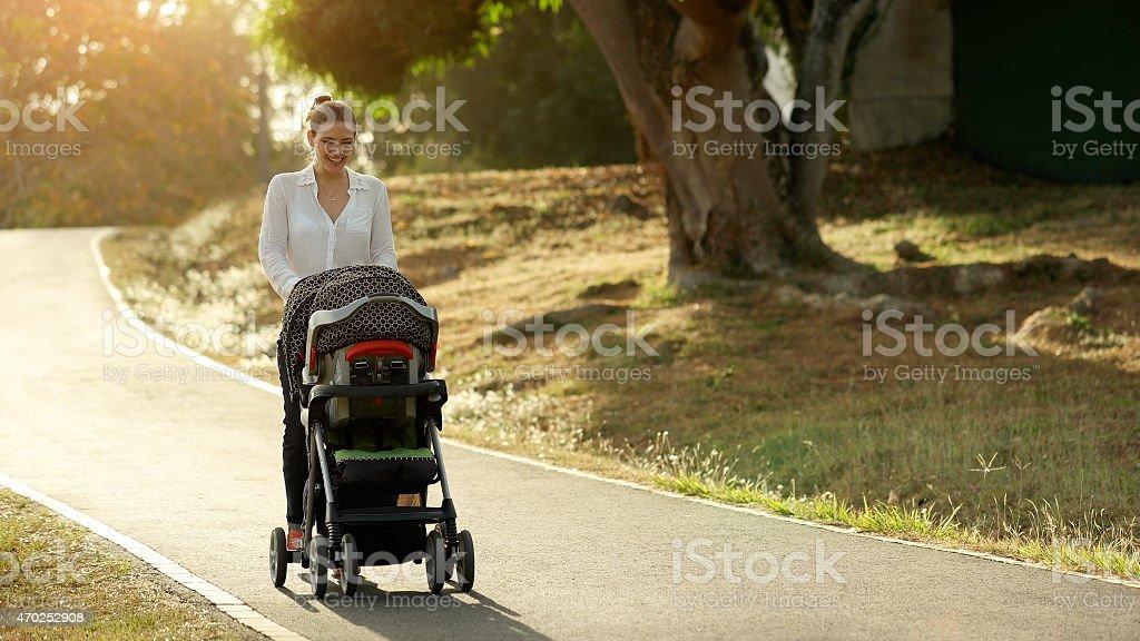 Mujer con niño en la madre Mom Pushchair caminando en el parque - foto de stock