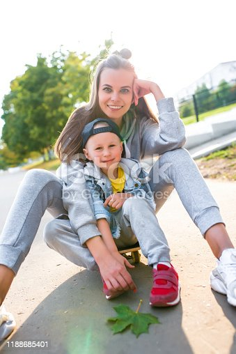 Woman mother sits on skateboard, funny people rejoice and laugh, little boy 3-5 years old, in summer in city, autumn, emotions of love, care, relaxation enjoyment. Weekend break with parent