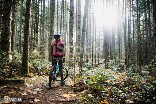 An adult woman pauses from a mountain bike ride to take in the beauty of her forest surroundings.  She smiles, enjoying the time outdoors.  Shot in Issaquah, Washington, USA.