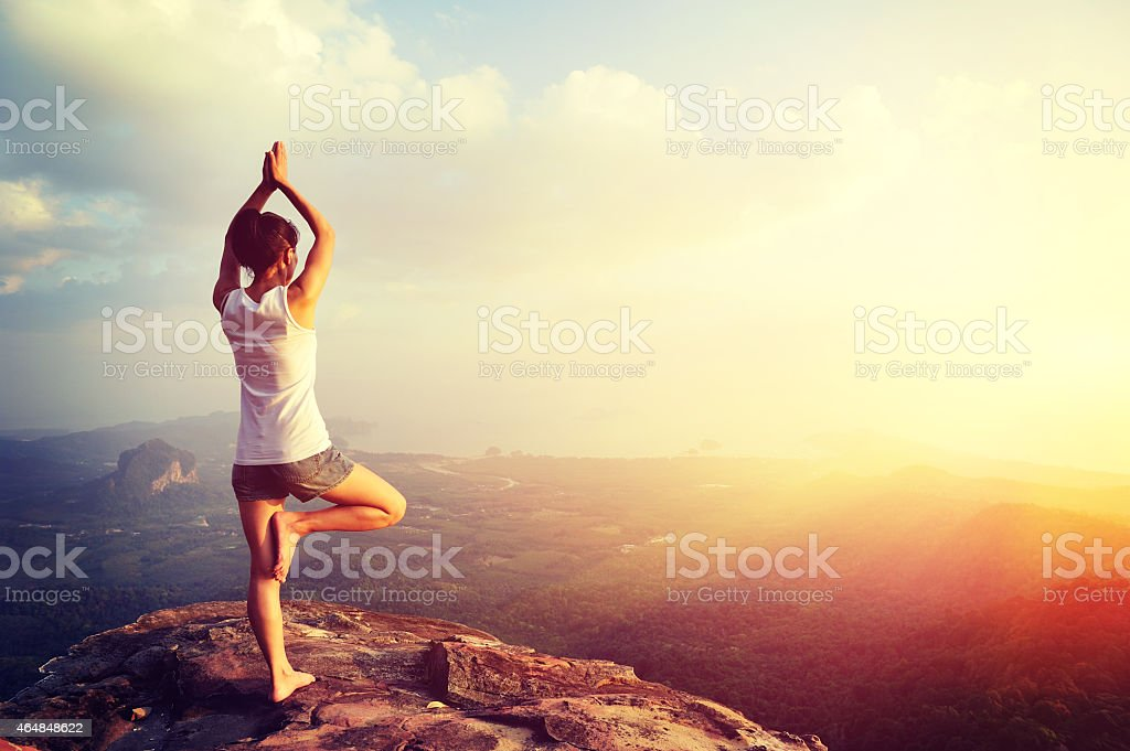 woman mountain peak cliff practice yoga stock photo