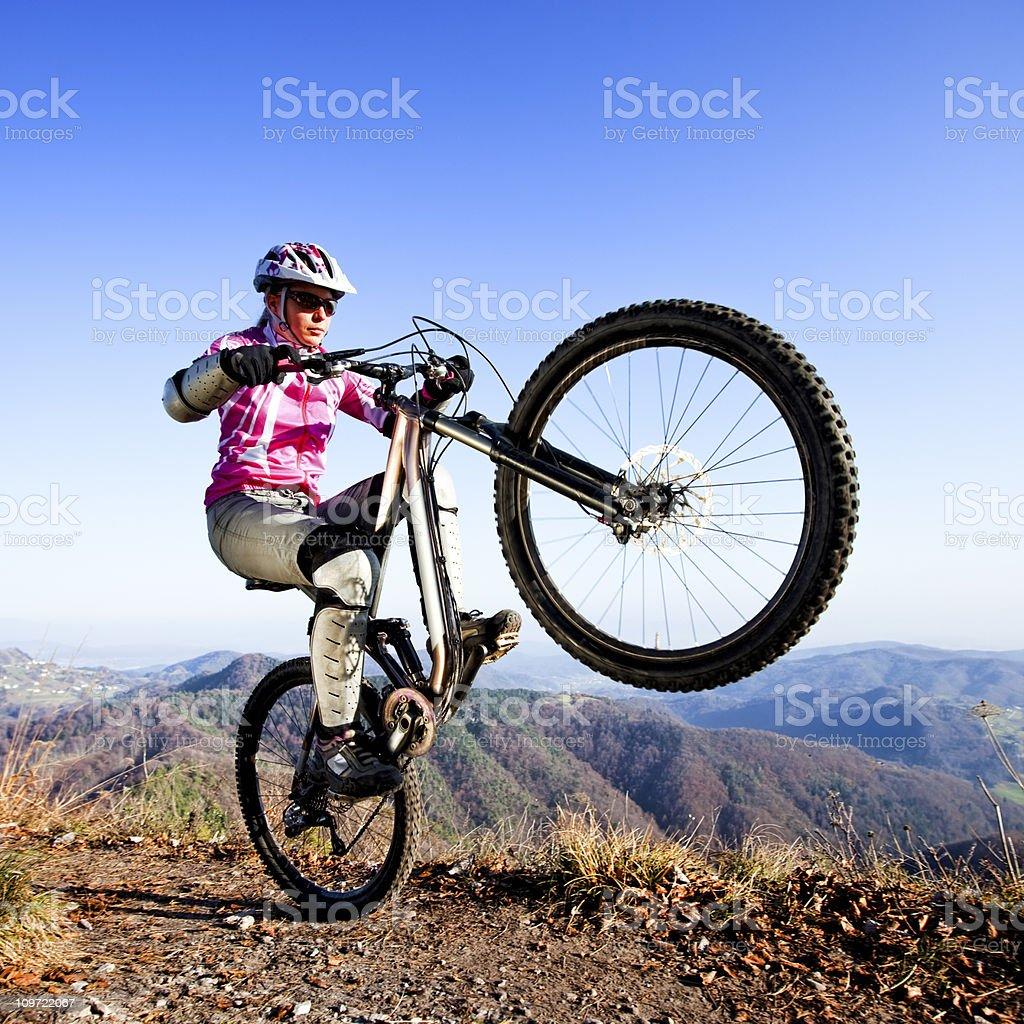 Woman mountainbiker riding a wheelie royalty-free stock photo
