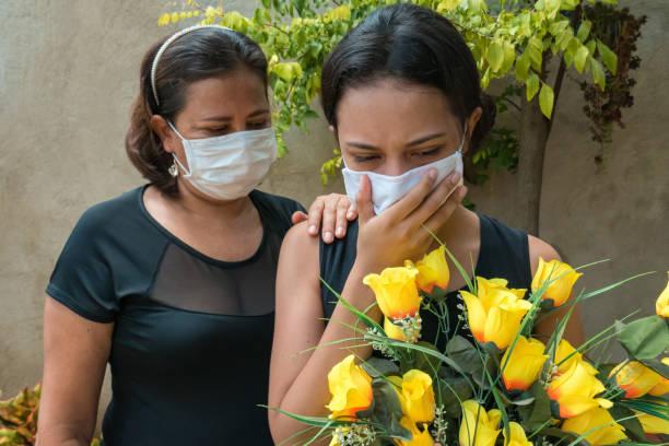 de rouwende vrouw, het dragen van zwart en het houden van bloemen, zet iemand een hand op haar aan console - funeral crying stockfoto's en -beelden