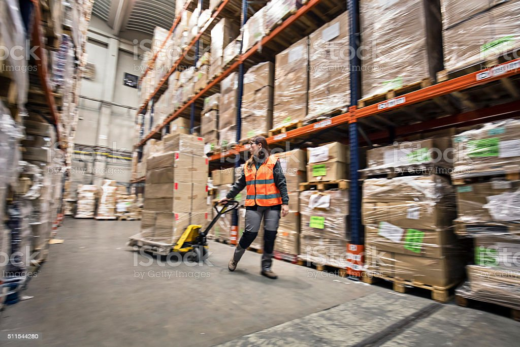 Woman moving boxes in a warehouse stock photo