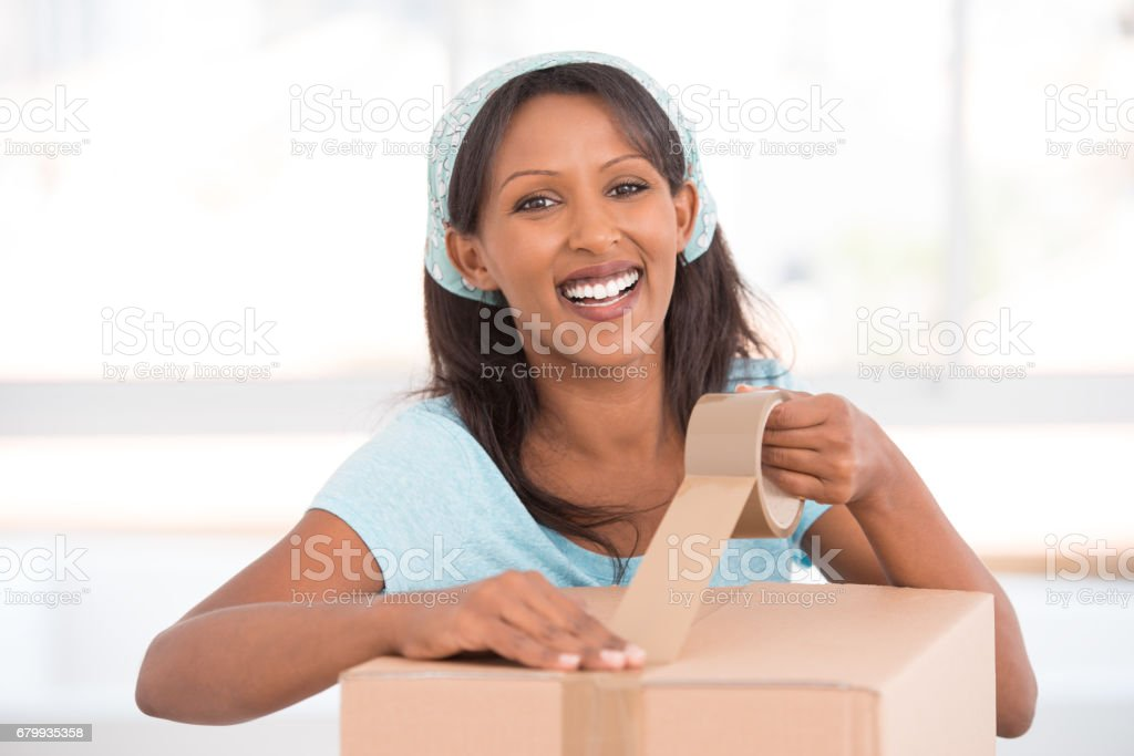 Woman moving to the new house, packing things. stock photo