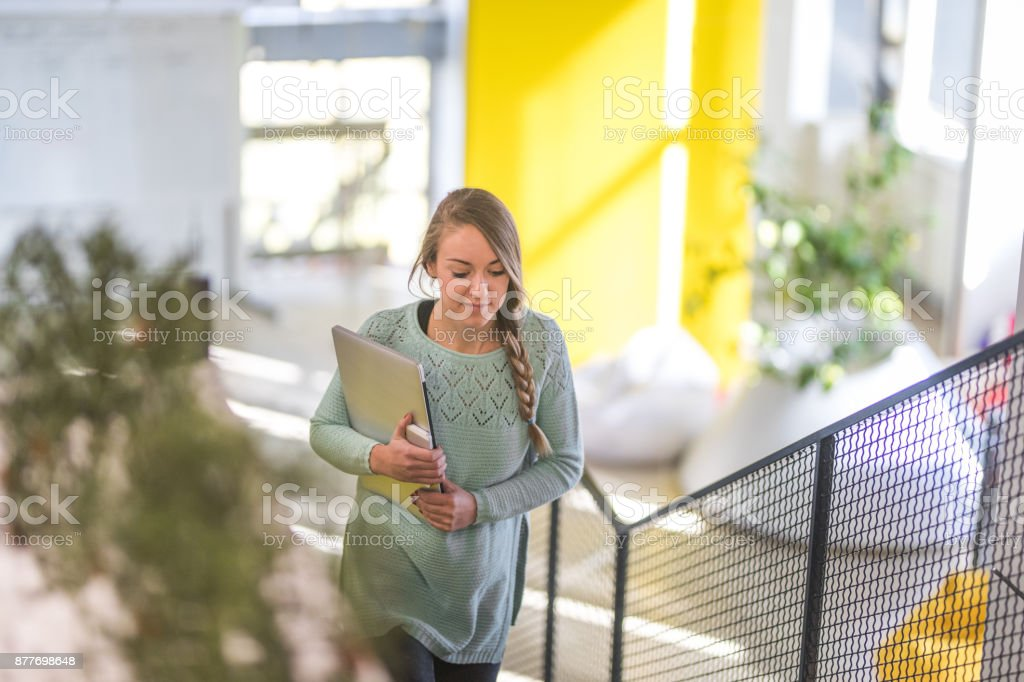 Woman moving up the stairs to go to the meeting in the office stock photo