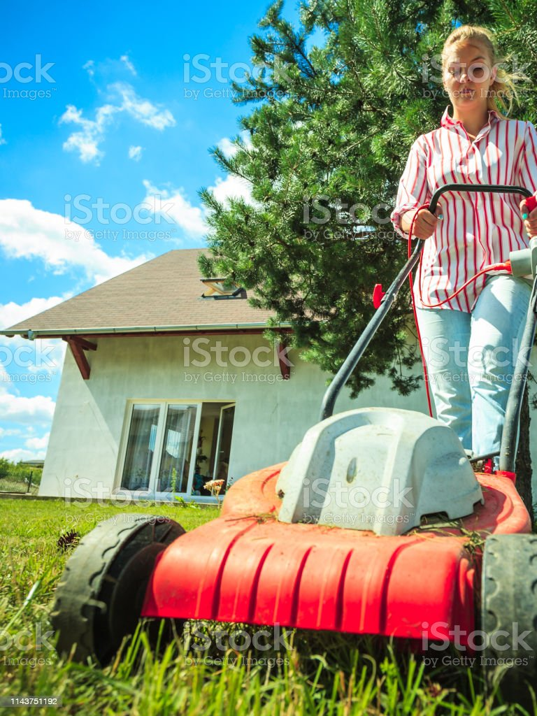Woman mowing lawn in the sun, Stock Photo, Picture And