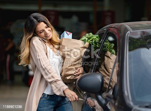 Happy woman multi-tasking getting in the car after shopping at the grocery store and talking on the phone – lifestyle concepts