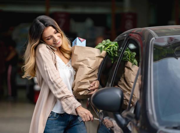 donna multitasking salire in macchina dopo aver fatto la spesa al negozio di alimentari - grocery home foto e immagini stock