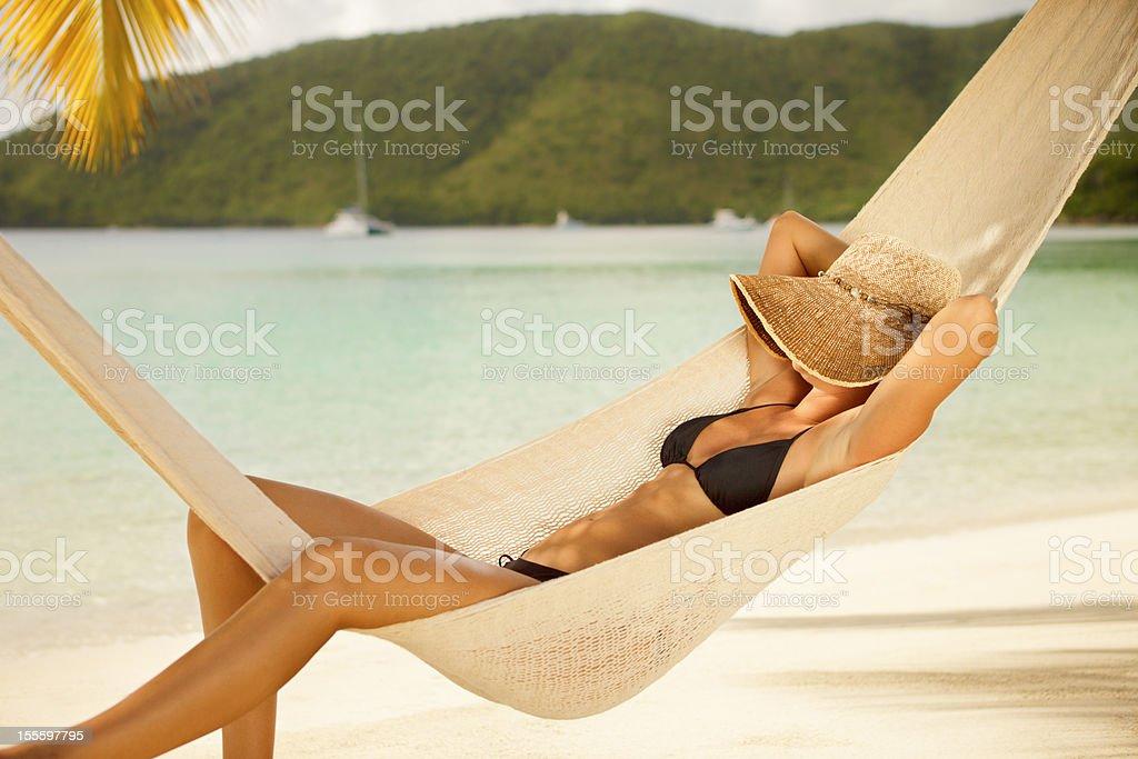 Cochilar mulher em rede na praia tropical no Caribe - foto de acervo