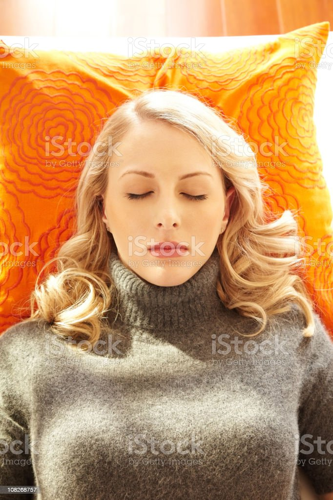 Woman napping on orange pillow royalty-free stock photo
