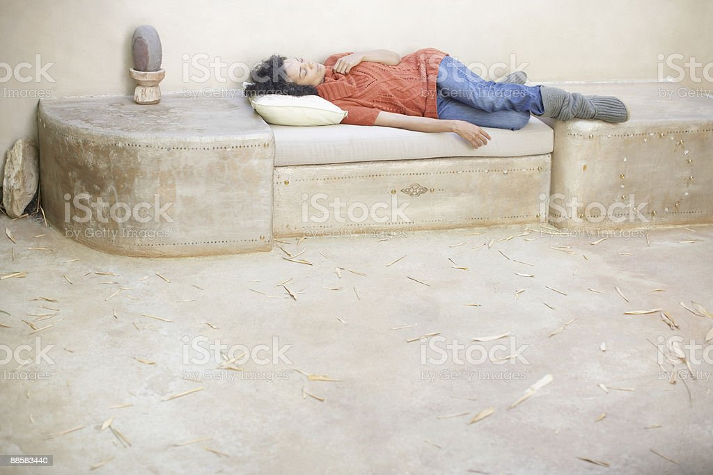 Woman napping on patio bench royalty-free stock photo