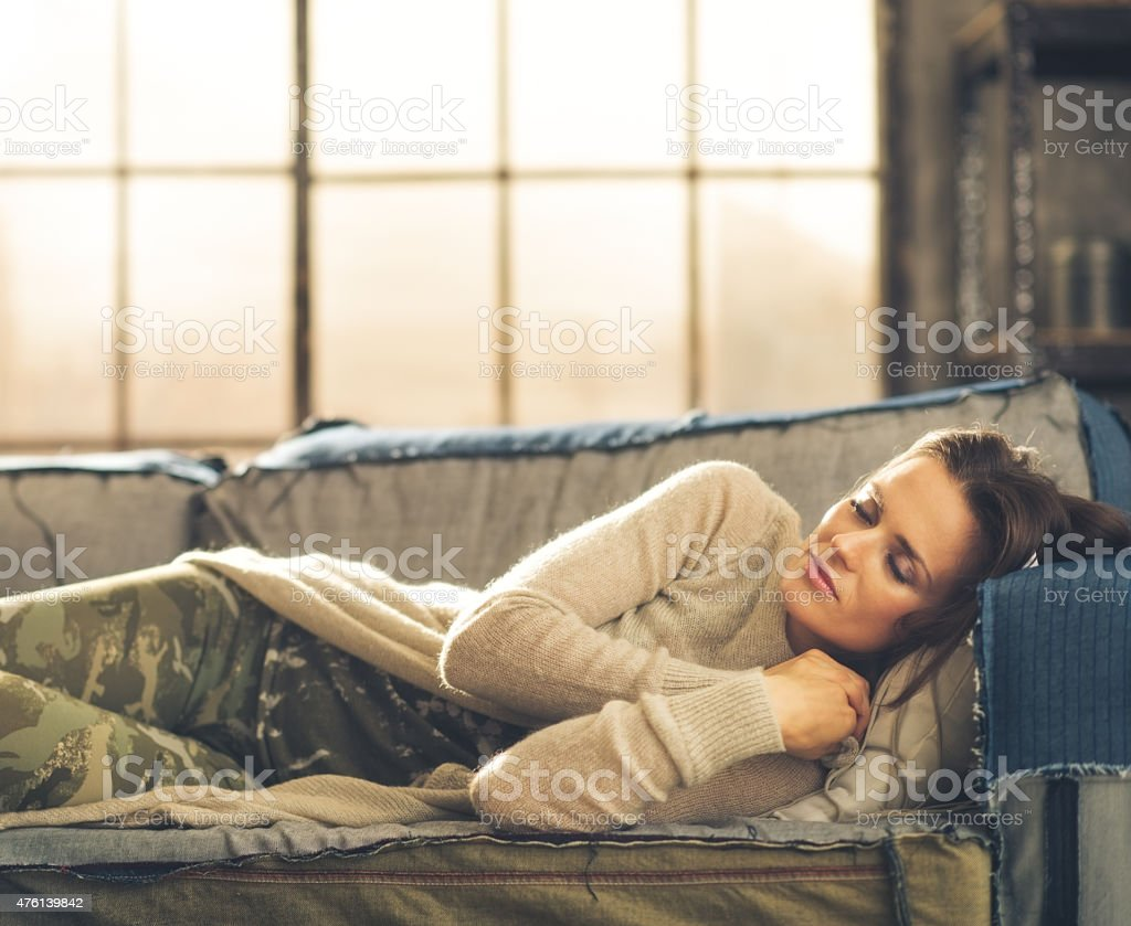 Woman napping on sofa in a city loft stock photo