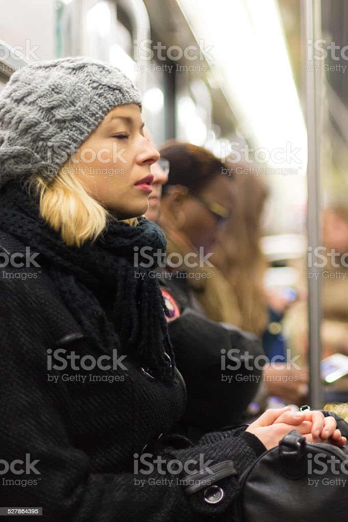 Woman napping on subway full of people. stock photo