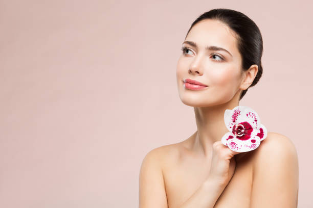 Woman Natural Beauty Makeup Portrait with Flower on Shoulder, Beautiful Girl Skin Care and Treatment stock photo
