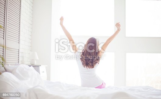 532275426 istock photo woman near big windows stretching after wake up 694760250