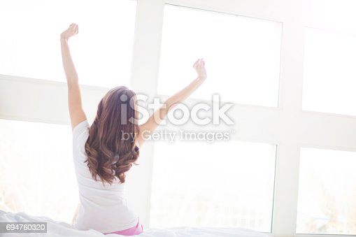 istock woman near big windows stretching after wake up 694760320