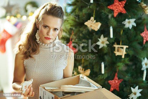 1059144984 istock photo woman near Christmas tree pulling out broken dish from parcel 1059144984