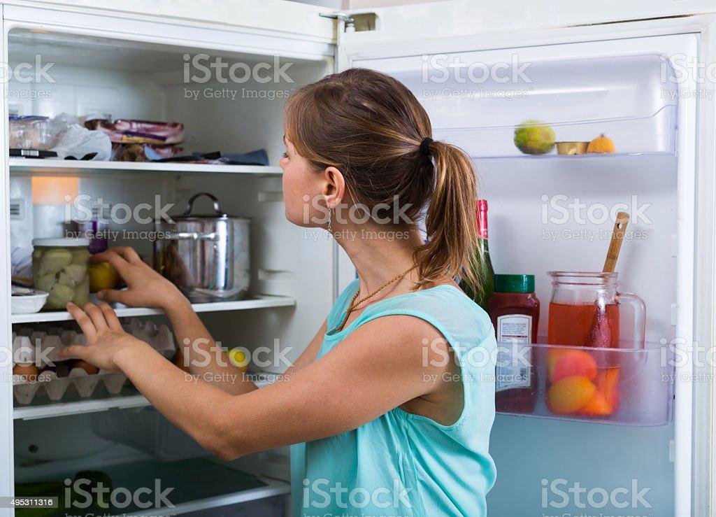Woman near full fridge stock photo