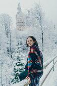 Schwangau, Germany - November 29, 2017: Young Caucasian woman walking in the park near Neuschwanstein castle in Germany in winter