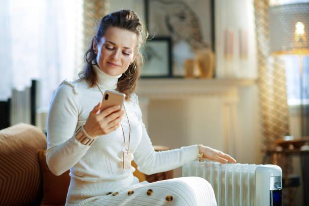woman near radiator using smartphone app for temperature control stock photo