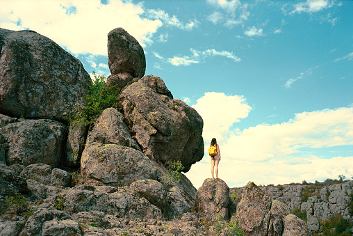 Young Caucasian woman near rock formation in summer