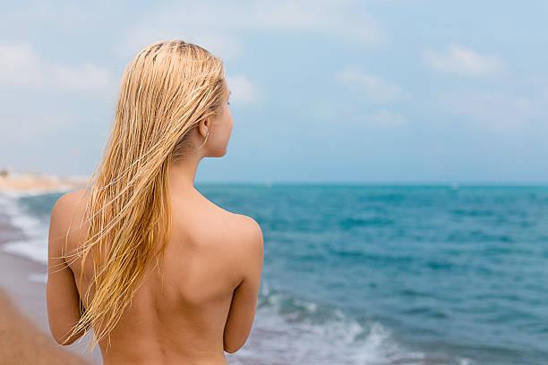 frau in der nähe von meer - fkk strand stock-fotos und bilder