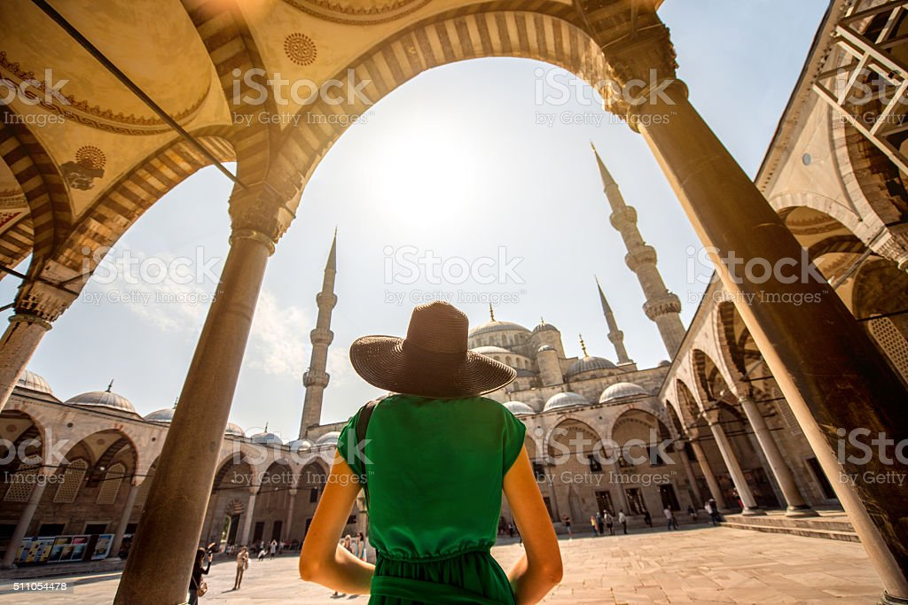 Woman near the Blue Mosque in Istanbul Young woman traveler in black hat and green dress looking on amazing Blue Mosque in Istanbul, Turkey Adult Stock Photo