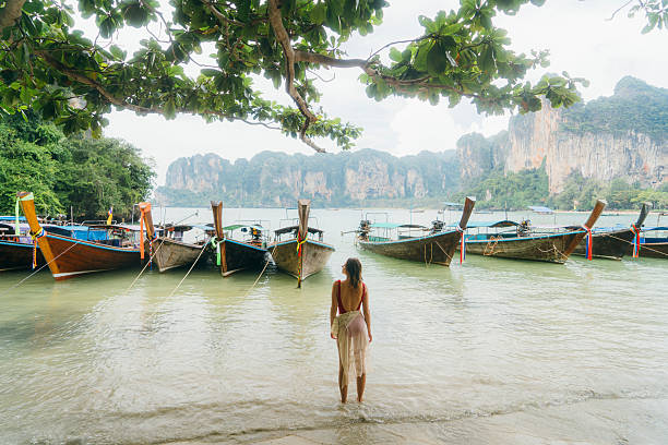 Woman near the boats on beach in Thailand stock photo