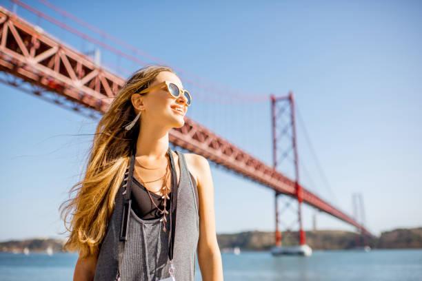 frau in der nähe der brücke in lissabon, portugal - lissabon reise stock-fotos und bilder