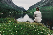 Young caucasian woman sitting near the mountain lake in Norway