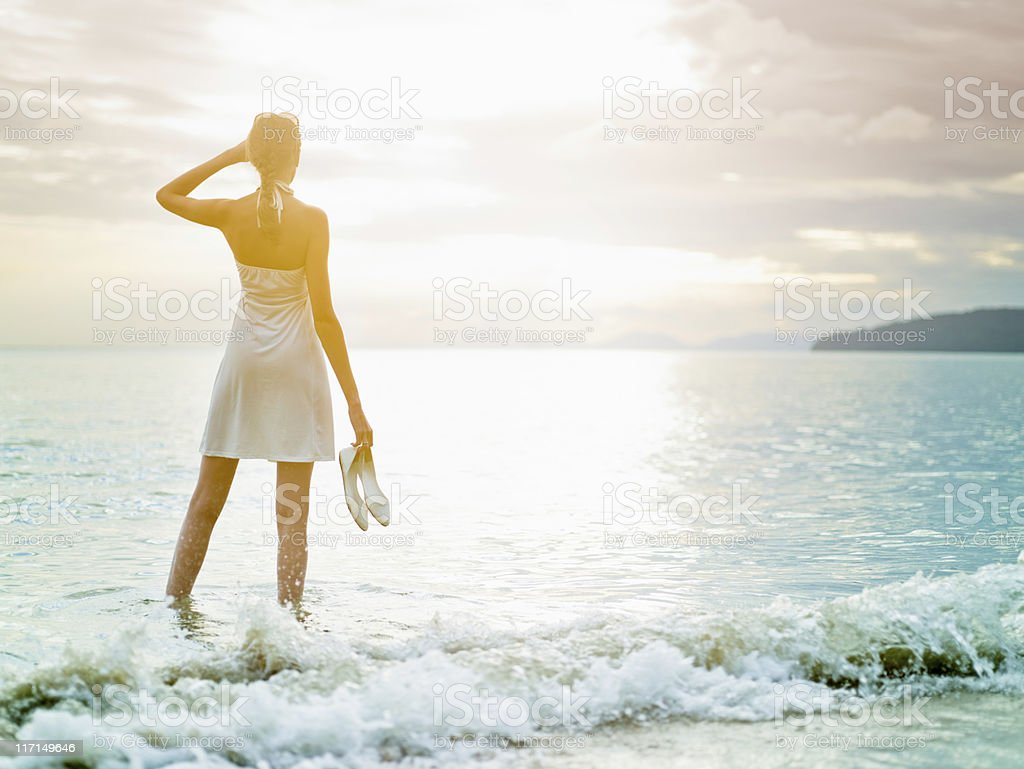 Woman near the ocean. Sunset time. stock photo