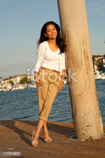 Beautiful ethnic woman enjoying the coast. View More: