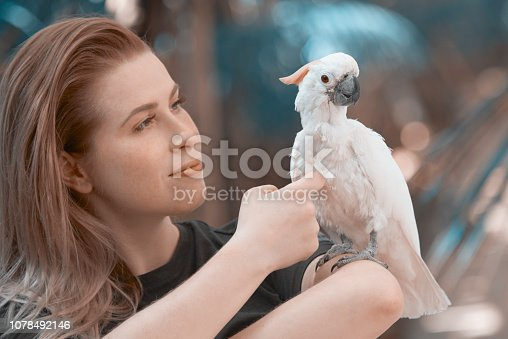 lifestyle shot of young woman near tropical white parrot enjoying spring day.