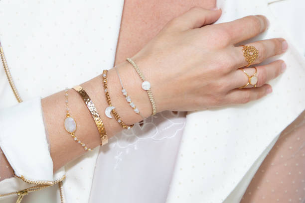 woman neck with hand with many bracelets - браслет стоковые фото и изображения