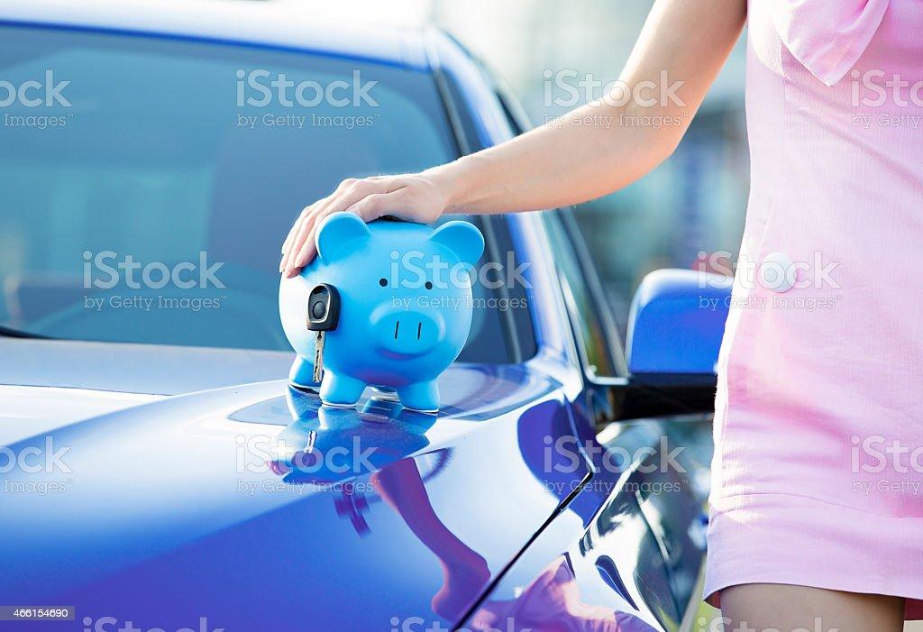woman new car, piggy bank, key on hood stock photo