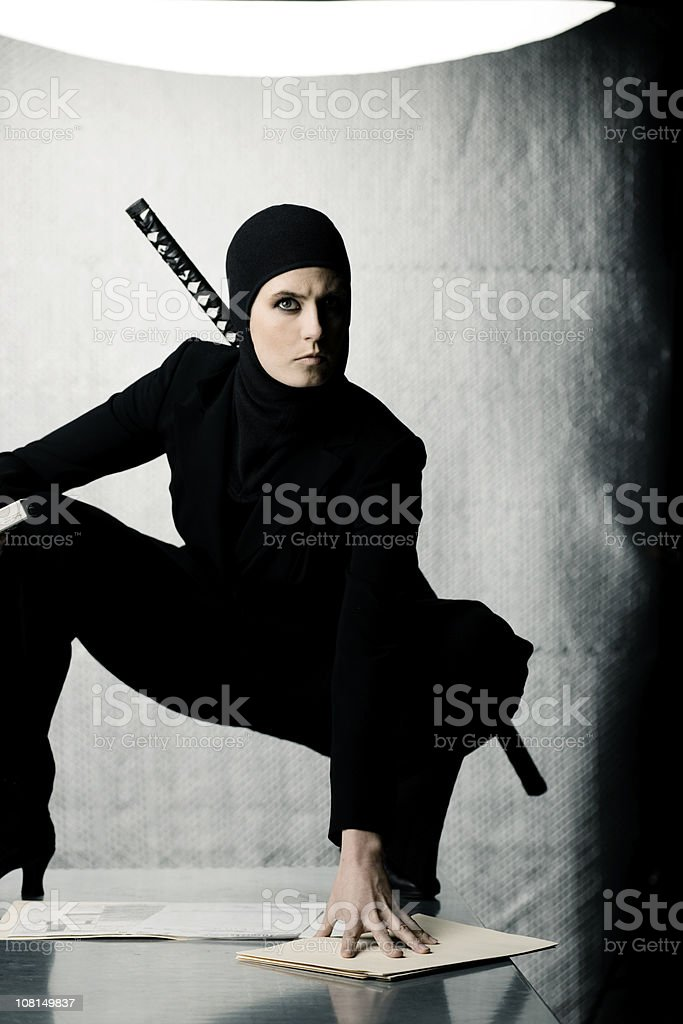 Woman Ninja Standing on Table Covered in Documents stock photo