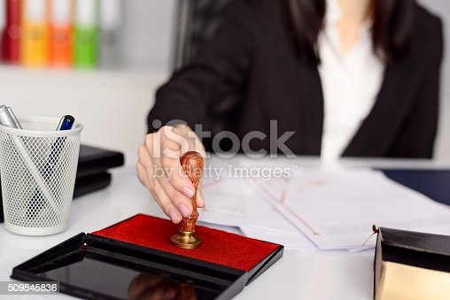 854317150istockphoto Woman notary public reaches her stamp 509545836