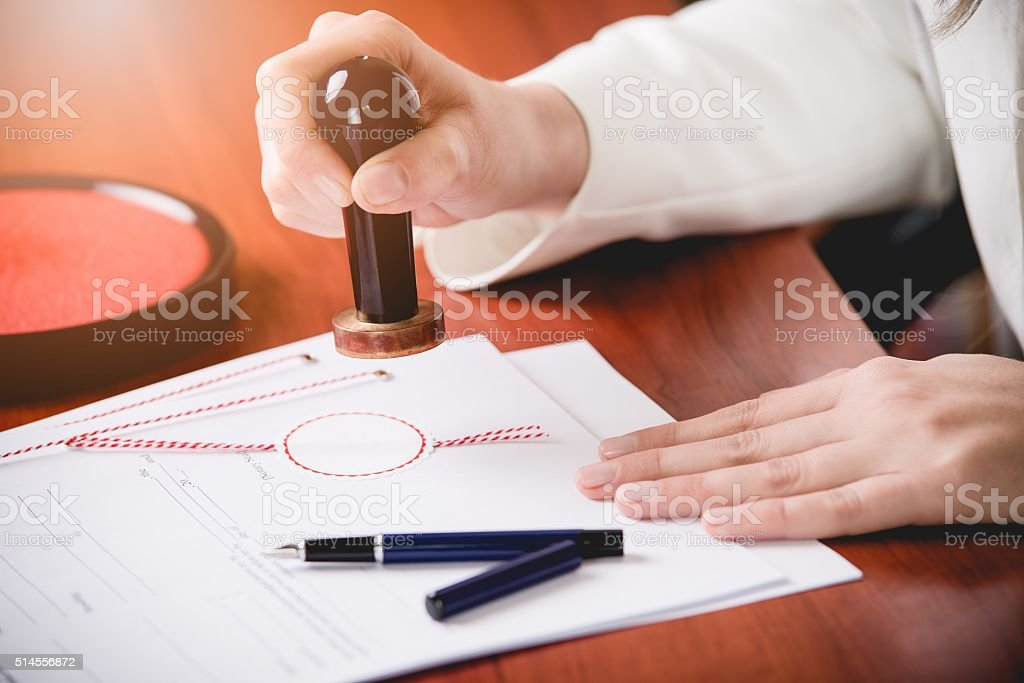 Woman Notary Public stamping the contract stock photo
