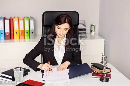 854317150istockphoto Woman notary public stamping the document in her office. 508758706
