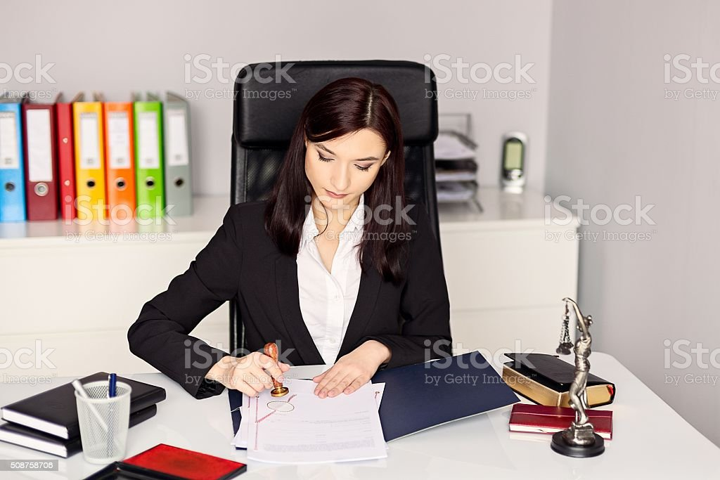 Woman notary public stamping the document in her office. stock photo