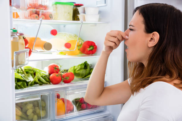 Woman Noticed Smell In Front Of Refrigerator stock photo