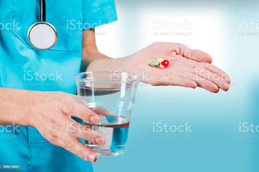 woman nurse or doctor hands close up while serving pills and a cup of water stock photo